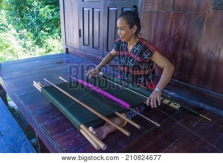 QUANG NAM VIETNAM - OCT 07 : Woman from the Cotu Minority weaves with a strap loom in Quang Nam Vietnam on October 07 2017. The Cotu minority mostly live in central Vietnam