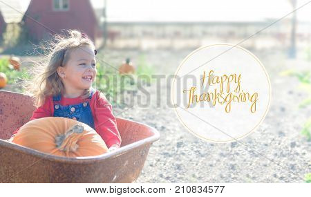 Little girl in red outfit sitting inside old wheelbarrow with big pumpkin at farm field pumpkin patch, smiling happily. Happy Thanksgiving card.