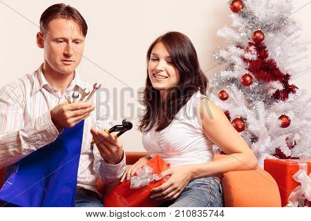 a young couple is sitting on the couch and exchanging christmas gifts. he doesn't seem to be very happy about his new toolset and all the repairs he is supposed to do with them.