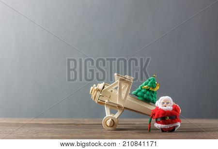 Decoration & Ornament merry Christmas and Happy new year concept.Santa Claus and airplane transfer offloading fir tree.Essential accessories on modern brown rustic wooden at home office desk.