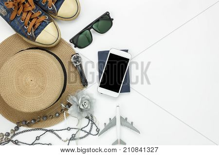Table top view of accessory travel and fashion women with technology concept background.Difference objects for traveler with copy space.Essential items for trip on the white wooden at office desk
