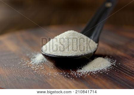 Organic semolina or couscous wheat in black spoon on wooden background.