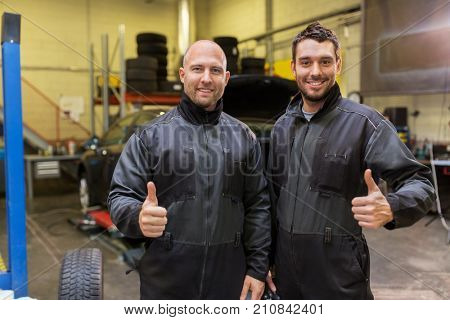 auto service, repair, maintenance and people concept - mechanics or tire changers at car shop