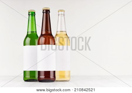 Three beer bottles longneck 500ml different colors with blank white label on white wooden board mock up. Template for advertising design branding identity.