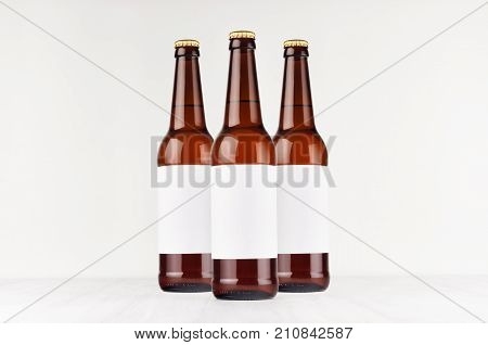 Three brown longneck beer bottles 500ml with blank white label on white wooden board mock up. Template for advertising design branding identity.