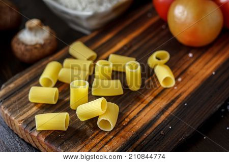 Raw Italian rigatoni pasta on wooden kitchen board