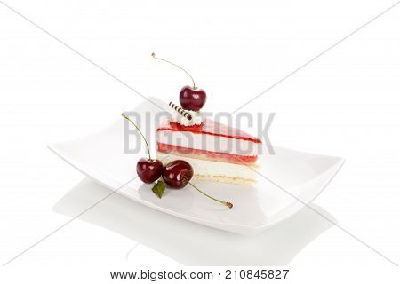 Delicious sweet cherry cake with cherries on white plate. Isolated on white background with reflection. Sweet dessert.