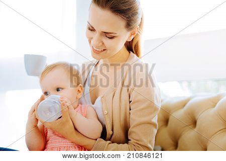 Careful drinking. Cute pretty baby girl drinking carefully from a little bottle while her mother helping her