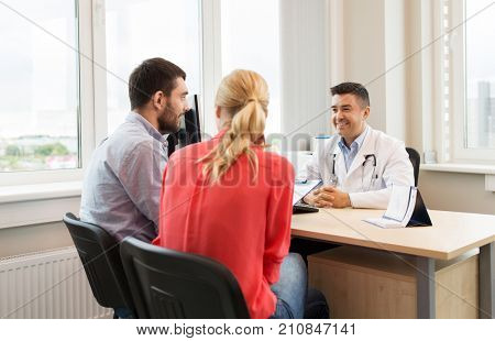 family planning, medicine, fertility and healthcare concept - couple visiting doctor and filling form at clinic