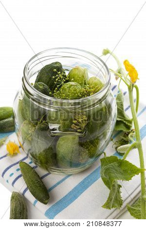 Pickles. Fresh cucumbers in glass on white wooden table on towel. Vintage rustic style. Preserved food.