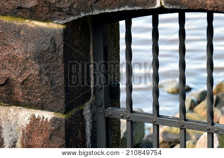 Close up of old prison bars and stone wall. Outside of the cell is stony beach and a sea.