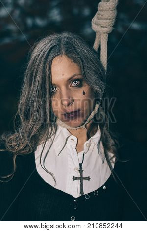 Suicidal woman hanging on hanging rope. Halloween concept.