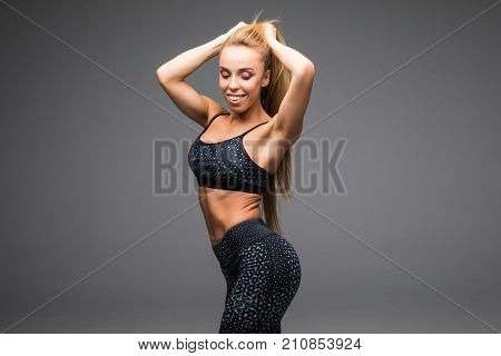 Fit Beautiful And Young Athletic Woman Standing In A Relaxed Pose, Big Smile And Wearing A Grey And