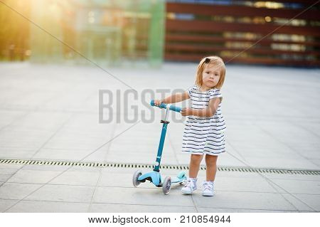 Portrait of a two year old girl with the scooter. Nice face short blond hair serious look. Cute baby holds with hands the blue children's scooter.