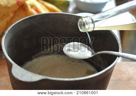 Process Of Quenching The Baking Soda With The Vinegar In A Spoon Over A Cast-iron Bowl With A Batter