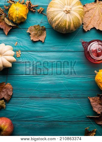 Moody green autumn background with pumpkin, apples, yellow leaves. Fall still life flat lay. Copy space frame