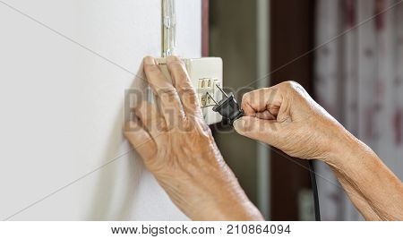 Elderly woman trying plug cable to the electric outlet