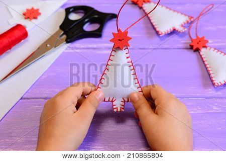 Child holds a felt Christmas tree decoration in his hands. Child made Christmas decorations from felt. Handicraft materials and tools on a wooden table. Hand sewing lesson for kids on winter holidays