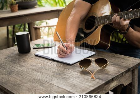 man compose song and play guitar on wood table