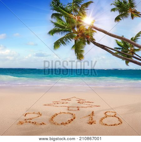 New Year 2018 is coming concept. Happy New Year 2018 .Written 2018 on the beach Christmas tree.