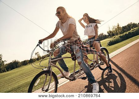 Carefree couple. Beautiful young couple in casual wear cycling together while spending carefree time outdoors