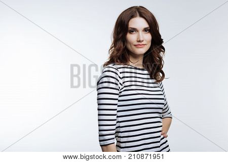 Beauty of model. Gorgeous young woman with an auburn hair wearing a striped pullover and posing against a white background