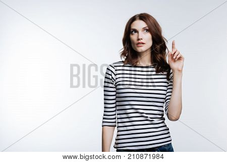 How could I forget. Beautiful young woman with an auburn hair raising her finger, having remembered to do something important while standing against a white background