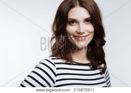 Sweet smile. Beautiful young woman with an auburn hair smiling at the camera while posing against a white background