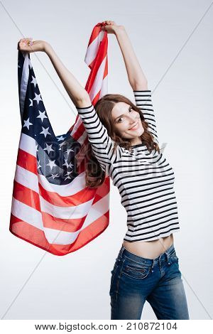 Proud patriot. Beautiful slim auburn-haired woman in a striped pullover lifting up an American flag high above her head while posing with it against a white background