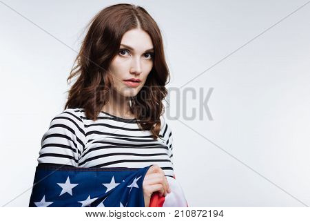 Love my country. Gorgeous auburn-haired woman in a striped pullover posing against a white background while being wrapped in an American flag