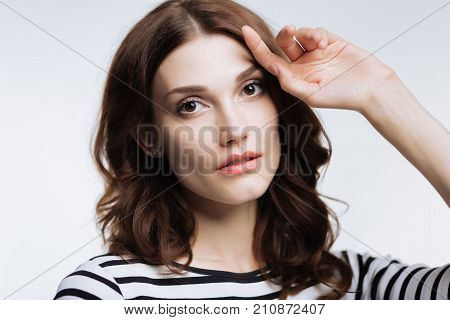 Enchanting beauty. The close up of a pretty auburn-haired young woman in a striped pullover posing against a white background and looking at the camera