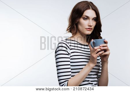 Need more sleep. Pleasant auburn-haired woman in a striped pullover drinking coffee, looking exhausted after a sleepless night