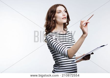Upsurge of inspiration. Pleasant young woman in a striped pullover writing in the air with her pencil while holding a sheet holder in her other hand
