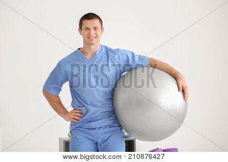 Young physiotherapist with fitball in rehabilitation center