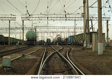 RUSSIA PERM - OCTOBER 23 2017: View of the classification yard from one of the tracks. Divergent rails ends of freight cars and tank cars numerous electrical network designs.