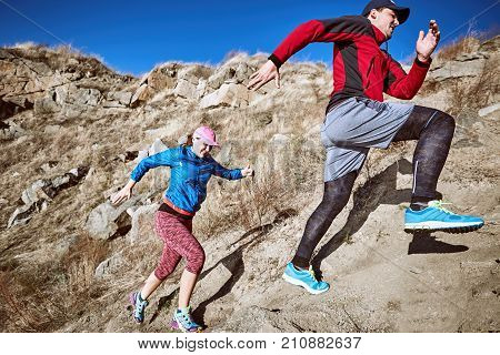 Trail running couple runners racing on mountain path in volcanic rocks .