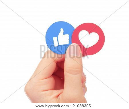 Kiev Ukraine - September 04 2017: Hand holds Facebook Like and Love Empathetic Emoji Reactions printed on paper. Facebook is a well-known social networking service