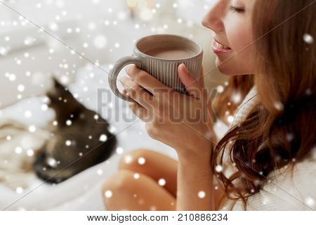 winter, cosiness, leisure and people concept - close up of happy young woman with cup of coffee or cacao and cat at home over snow