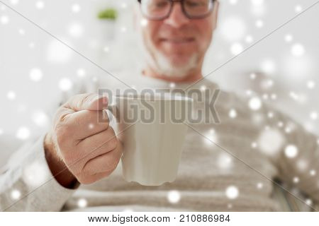 old age, drink and people concept - happy senior man with cup of tea or coffee at home over snow