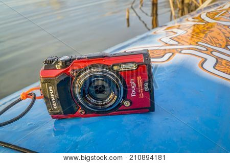 Fort Collins, CO, USA - October 23, 2017: Compact, waterproof Olympus Stylus Tough TG-5 camera on a wet deck of a stand up paddleboard by Starboard.