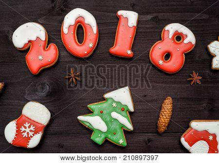 Christmas tasty homemade gingerbread cookies on wooden table top view. New year 2018 baked candy numbers with star anise and cone flat lay. Christmas tree sock house. Christmas cookies