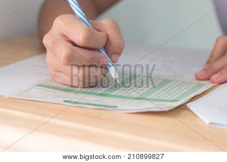 Students holding pencil in hands taking exams multiple-choice quizzes or testing exam answer sheets exercises on wood table in secondary school college university classroom Education concept