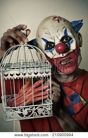 closeup of a scary evil clown with a bloody amputated hand in a birdcage
