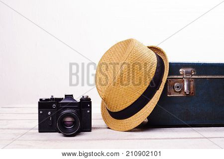 Vintage male travel set. straw hat old suitcase and camera on white wooden floor near wall