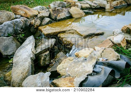 waterfall of stones with a fountain with water and decorative installation on the pond