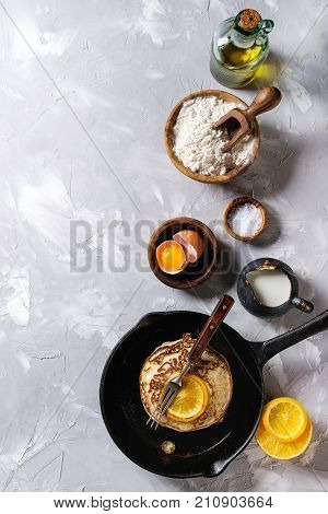 Homemade pancakes with fried orange in cast-iron pan and ingredients above. Wooden bowls of flour, yolk, salt, milk, olive oil over gray texture background. Top view with space. Home cooking concept