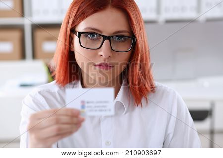 Female hand in suit give blank calling card to visitor closeup. White collar partners company name exchange executive or ceo introducing at conference product consultant sale clerk concept