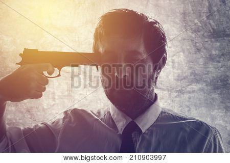 Businessman points gun to his head disappointed suicidal man about to commit a suicide. Unemployment and business failure concept.