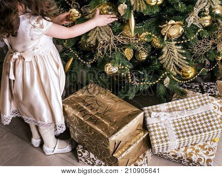 A girl is decorating Christmas tree with glass Christmas balls and toys. Preparing for Christmas and New Year holidays.