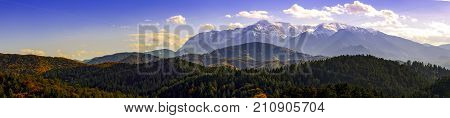 panoramic view of bucegi mountains covered in snow and autumn foliage from rasnov,  at brasov county romania europe